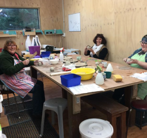people sat at a table learning about ceramic pottery.