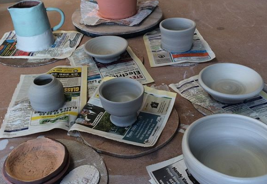 table covered in ceramic pottery in various stages of completion.