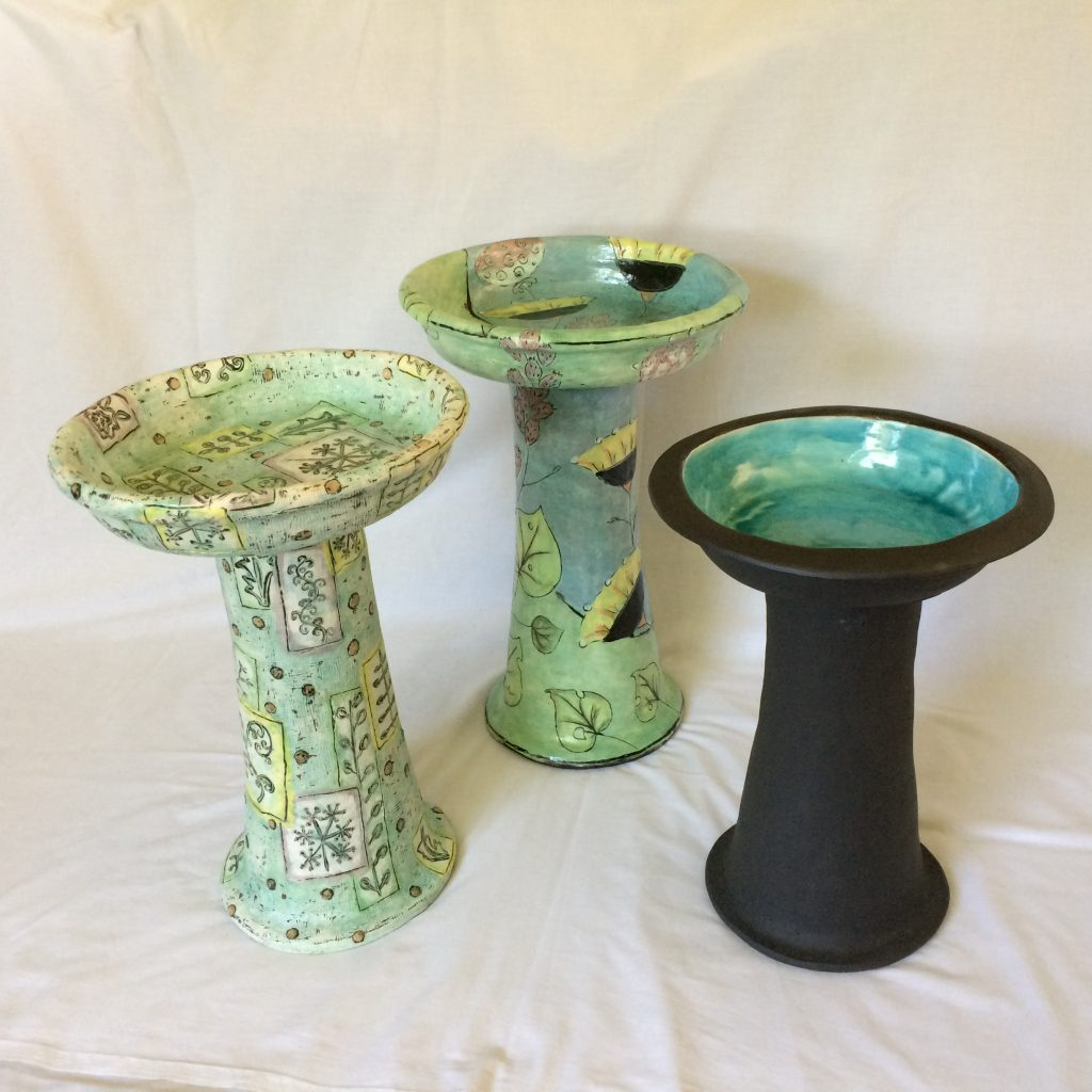 three ceramic bird baths in hues of green.